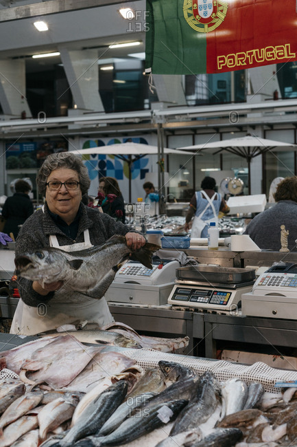 Porto, Portugal - March 3, 2017: Woman holding a large whole fish at a market