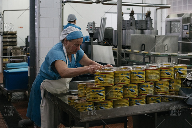 Porto, Portugal - March 3, 2017: Woman preparing cans of tuna at a processing plant