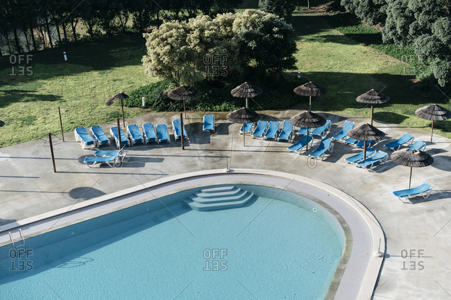 Lounge chairs around an empty swimming pool at a resort
