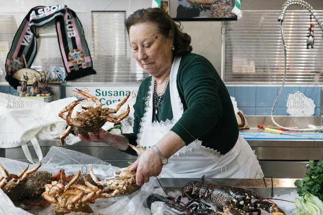 Porto, Portugal - March 4, 2017: Woman preparing shellfish in a kitchen