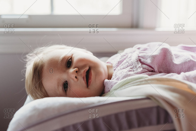 Happy baby girl lying on changing mat
