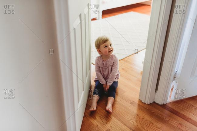 Toddler girl sitting on floor in doorway