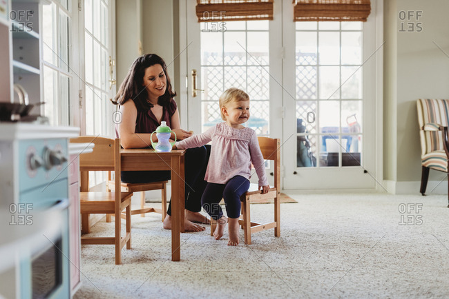 Woman sits with her toddler daughter at table and chairs