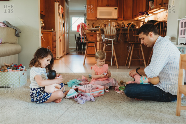 Father plays with dolls with two young daughters
