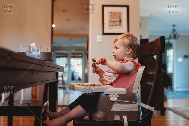 Toddler girl eating in booster seat