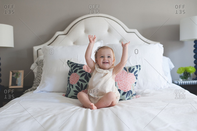 Cute toddler girl with hands up on white bed