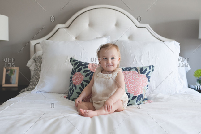 Portrait of cute toddler girl on white bed