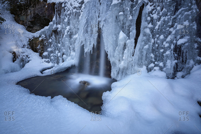 Details of a waterfall framed by ice and snow, Switzerland, Europe