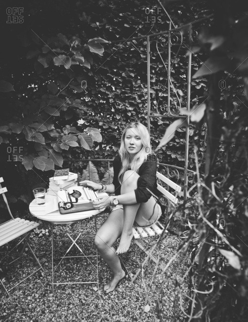 Young woman with typewriter sitting in the garden