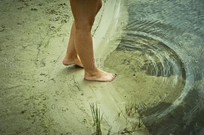 Barefoot woman at the lake shore