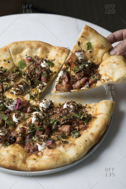 Hand grabbing pulled pork pizza