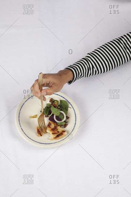 Person's hand eating from plate