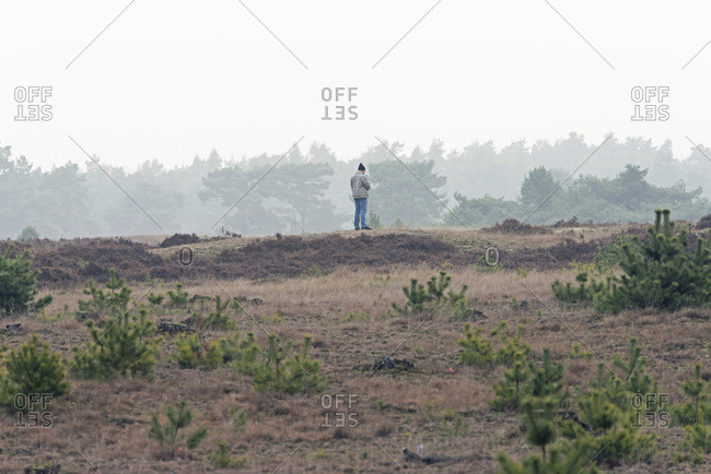 Man with woolen cap standing in misty moorland