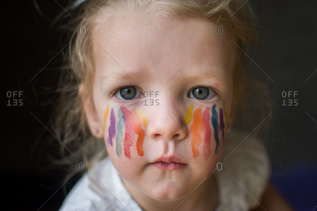 Toddler girl with streaks of paint on her face
