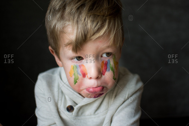 Pouting toddler boy with streaks of paint on his face