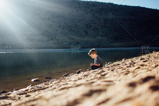 Preschool aged boy sitting at edge of lake