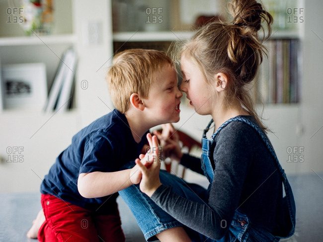 Two young siblings play together indoors