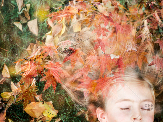 Girl lying on ground with autumn leaves in hair