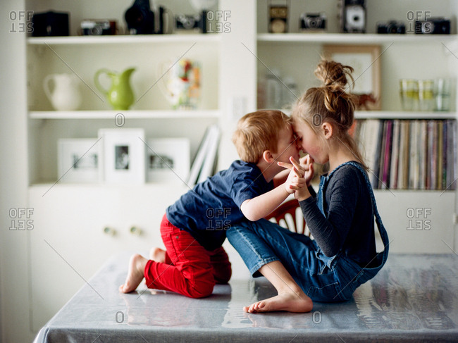 Two young siblings playing together on table