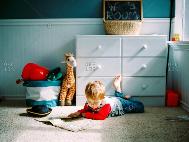 Young boy reading book on bedroom floor