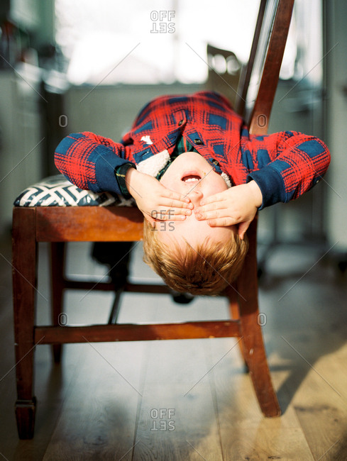 Boy covering his eyes while leaning off chair