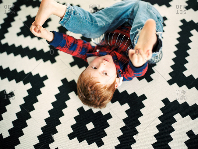 Young boy rolling on patterned carpet