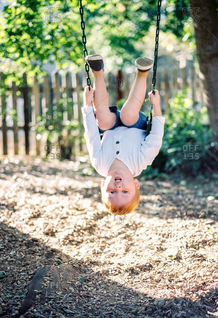 Boy hanging upside down on swing