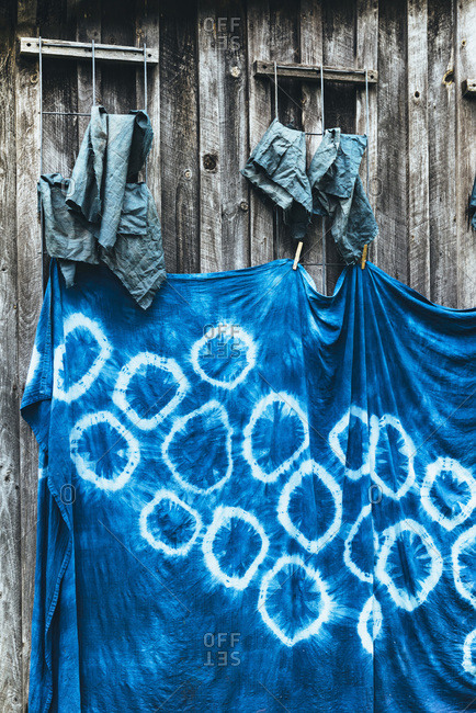 Tie dyed blue fabric hanging on wooden fence