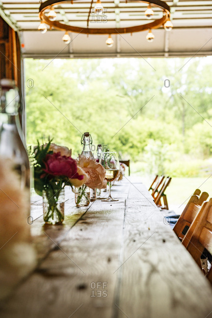 Rustic wood plank table set with flowers and wine