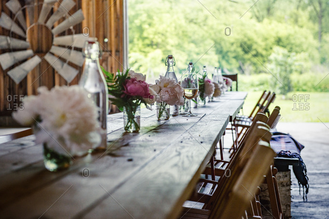 Rustic wood plank table set with peonies and wine