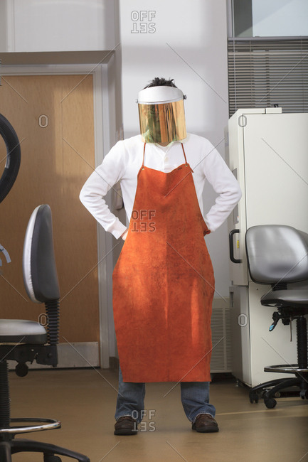 Engineering student wearing leather protective smock and splash guard in chemical analysis laboratory