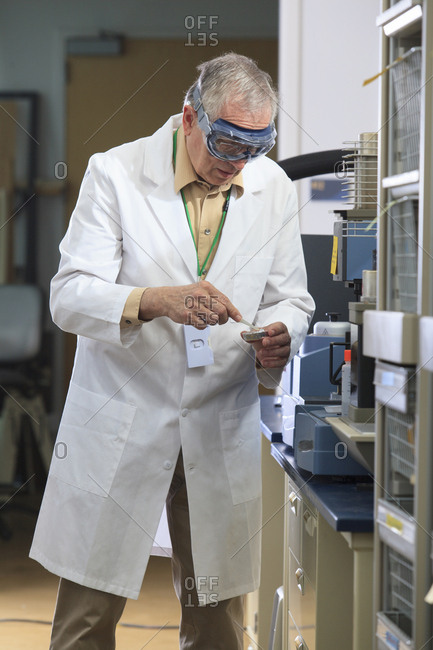 Professor wearing protective eyewear using tweezers to pick up reference sample for thermogravimetric analyzer in chemical laboratory