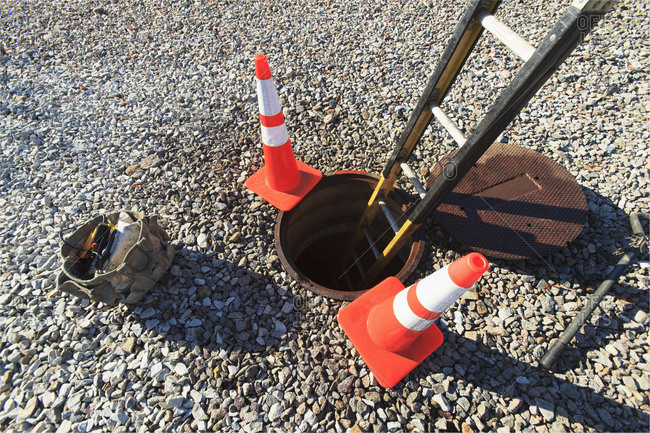 Ladder in manhole and warning cones at high voltage power distribution station, Braintree, Massachusetts, USA