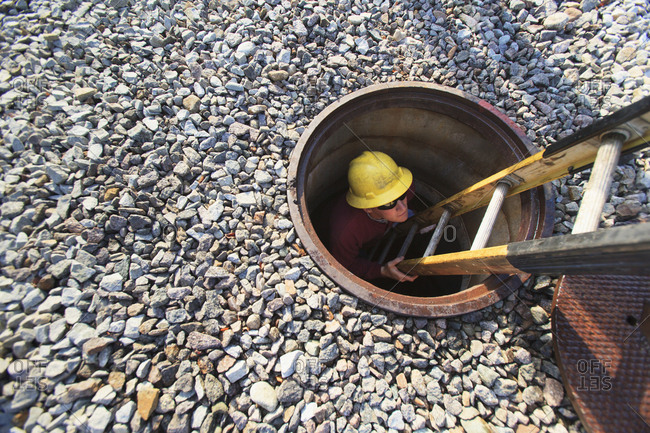 Power engineer inside climbing ladder in manhole at high voltage power distribution station, Braintree, Massachusetts, USA
