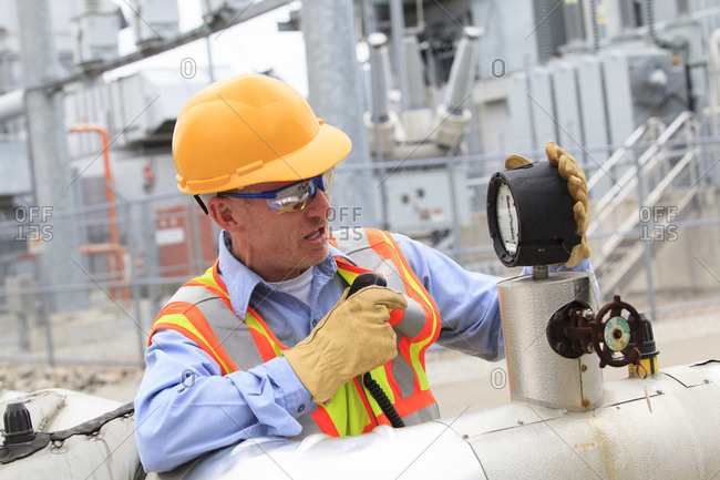 Electrical engineer examining pressure sensor at an electric power plant