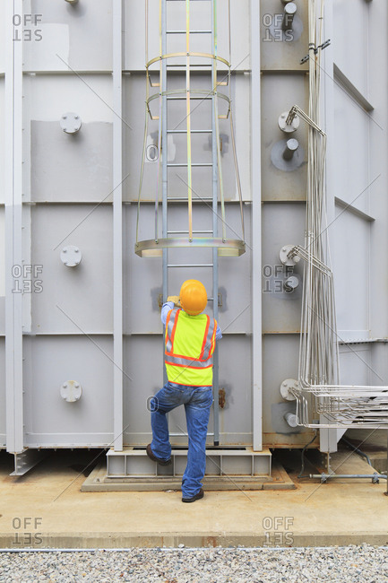 Engineer at sound suppression stage of gas turbine which drives generators in power plant while turbine is powered down