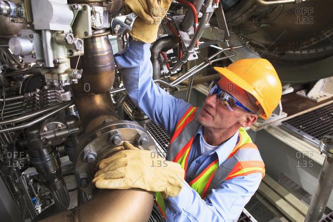 Engineer at turbine stage of gas turbine which drives generators in power plant while turbine is powered down