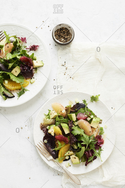 Two plates of mixed citrus avocado salad with greens