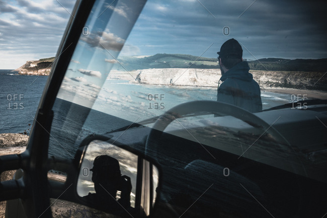 Man contemplates ocean through sky reflected on window of a van