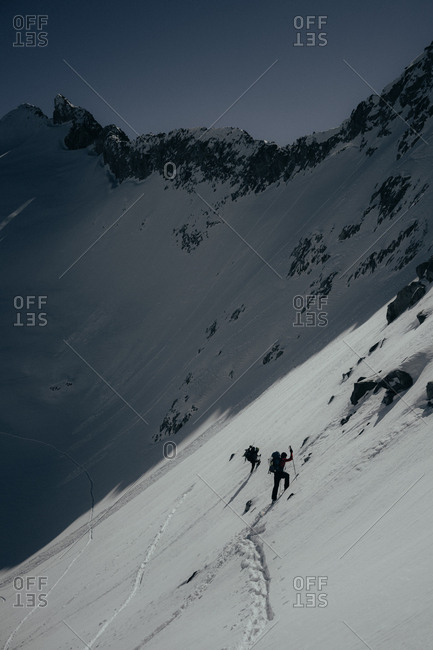 Ski mountaineers climbing steep face