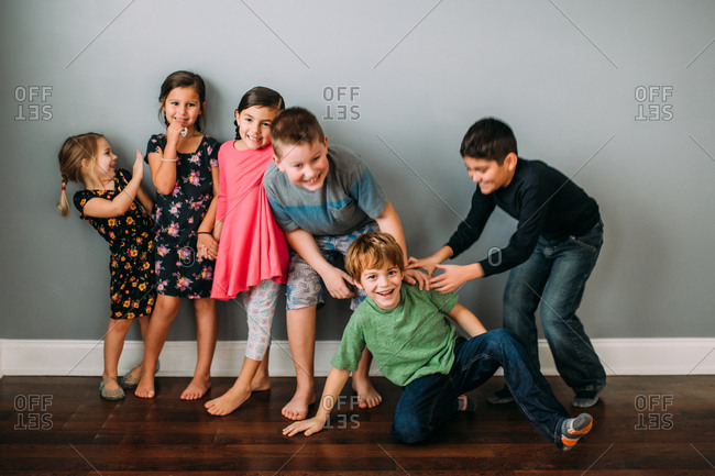 Group of kids in front of a gray wall goofing around