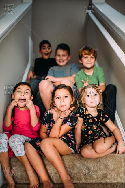 Group of kids sitting on stairs goofing around