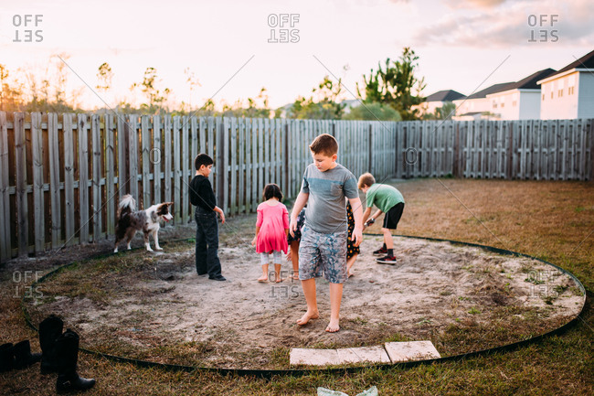 Children playing outdoors in a bare spot of a backyard