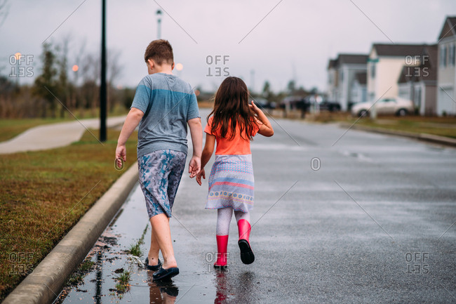 Two kids walking in street with rain puddles