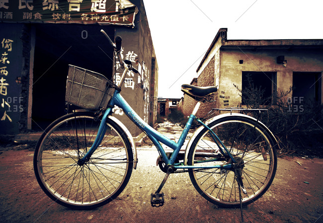 Beijing, China - October 16, 2010: Blue bike parked in front of abandoned buildings in Beijing, China