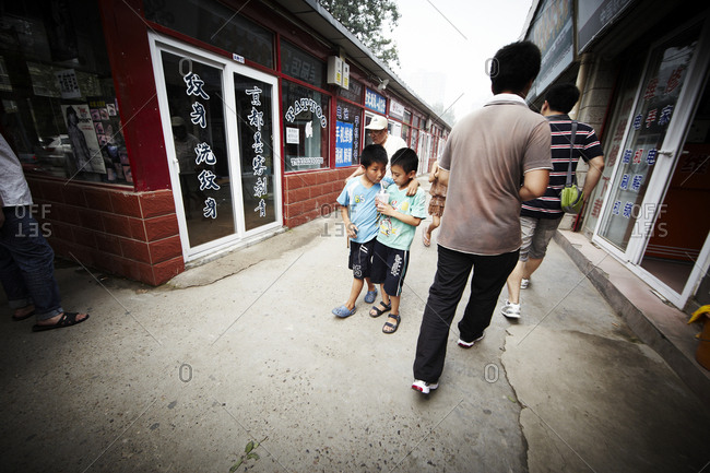 Beijing, China - July 22, 2011: Boys walking down the street sharing a drink in Beijing, China