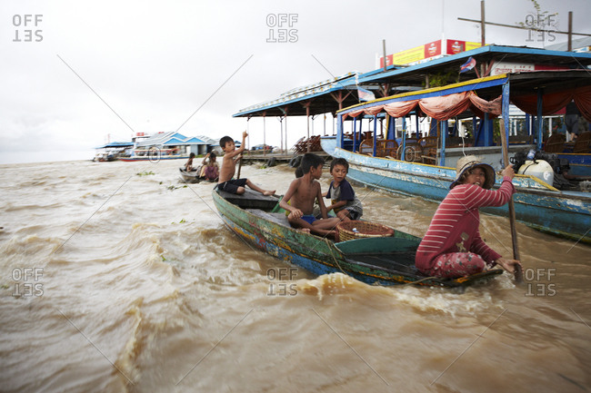 Siem Reap, Cambodia - July 10, 2012: Family riding on boat in the Tonle Sap Great Lake in Siem Reap