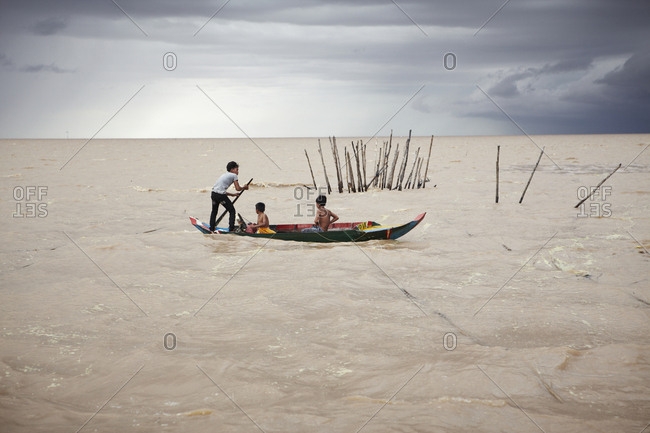 Siem Reap, Cambodia - July 10, 2012: Boys in a boat and on the Tonle Sap Great Lake
