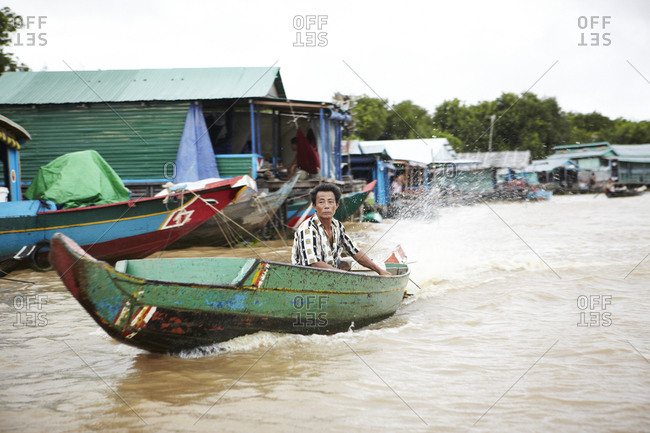 Siem Reap, Cambodia - July 10, 2012: Man riding on boat in the Tonle Sap Great Lake in Siem Reap