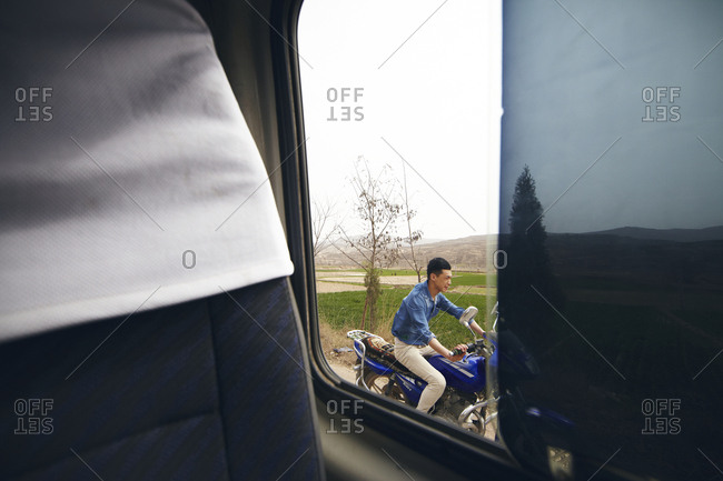 Gansu Province, China - March 21, 2013: View from van window of man riding motorbike in the Gansu Province, China
